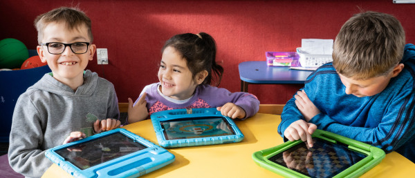 Kids with tablets at a table